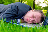 tired man asleep on a laptop in the park