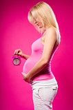 Pregnant woman holding alarm clock