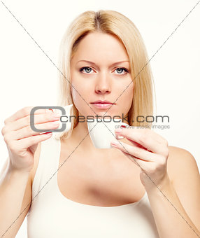 Attractive blond woman holding cup of coffee and cream