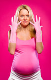 Pregnant attractive woman wearing rubber gloves posing over pink