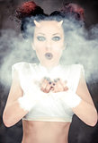 Portrait of devil woman blowing a white powder, conceptual photo