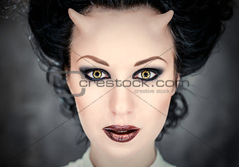 Portrait of beautiful horned woman with bright makeup