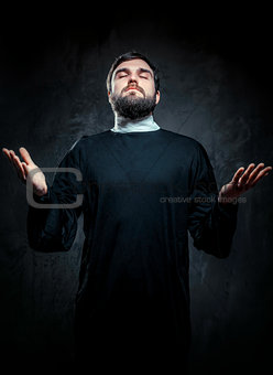 Portrait of priest against dark background