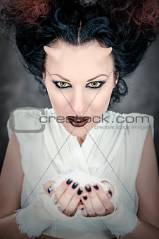 Portrait of devil woman holding heap of a white powder