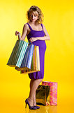 Beautiful pregnant woman looking inside shopping bags