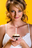 Beautiful young woman with birthday cake over yellow background