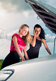 Two young women with broken car on a road