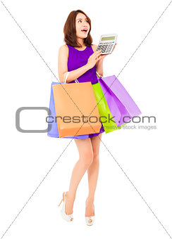 beautiful woman using a calculator and holding bags. isolated on