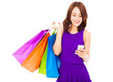 happy young woman holding shopping bags and mobile phone