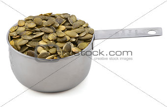Green pumpkin seeds in a cup measure