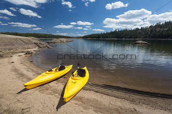 Pair of Yellow Kayaks on Beautiful Mountain Lake Shore.