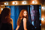 Portrait of lovely young redhead woman looking into mirror