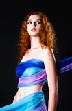 Studio portrait of beautiful young redhead woman covered in fabric