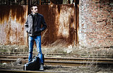 Young man with guitar case waiting for train among industrial ruins