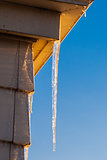 Icicle at house corner on clear sky.