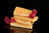 Delicious waffles with raspberries isolated on black.