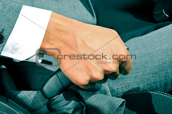 man in suit pulling the hand brake of a car