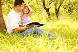 young father with his little daughter reading a book