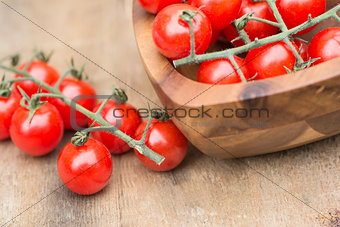Fresh cherry tomatoes in rustic vintage wooden bowl