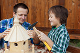 Father and son building a bird feeder