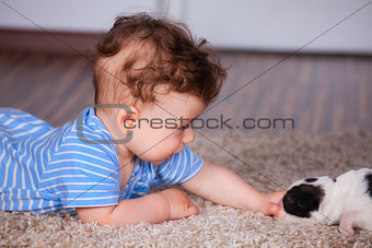 Baby boy playing with puppy