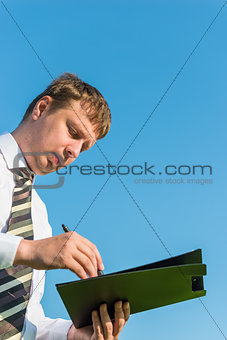 Businessman signs documents on sky background
