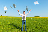 businessman in a tie throwing papers in the field