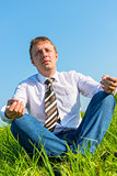 happy businessman relaxes in a field in the lotus position