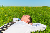 tired manager resting on green grass in field