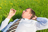businessman lying on the grass and sniffs dandelion