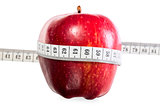 red ripe apple with a measuring tape on a white background