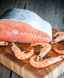 Raw salmon and shrimps on the wooden board