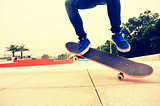 skateboarding woman jumping at outdoor skatepark