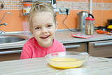 Girl eating porridge in the kitchen