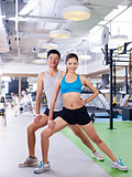 young man and woman working out in gym