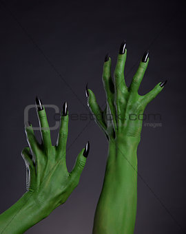 Green witch hands with black nails stretching up, real body-art