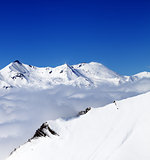 Mountains in clouds at nice day. View from ski slope.