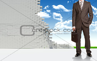 Businessman and ruined brick wall