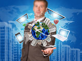 Businessman holding earth with electronics