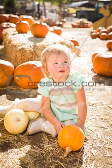 Adorable Baby Girl Holding a Pumpkin at the Pumpkin Patch