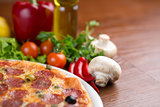 Salami pizza on table with vegetables and empty room