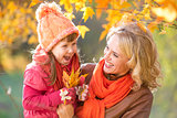 Happy parent and kid outdoor holding autumn yellow leaves
