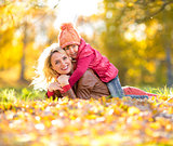 Parent and kid lying together on falling leaves. Happy family ou