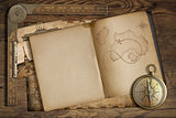 Vintage treasure map in open book with compass and old ruler. Ad