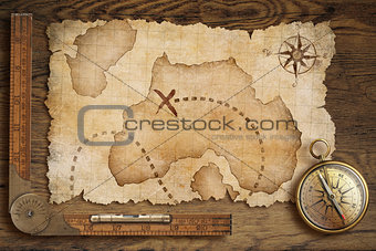 aged treasure map, ruler and old bronze compass on wooden table
