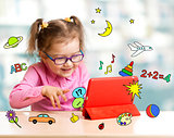Child sitting with tablet computer and learning or playing with