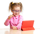happy child in glasses looking at mini tablet pc screen sitting