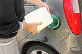 pouring gasoline into the gas tank from a white canister