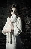 Horror shot: sad strange girl with moppet doll in hands