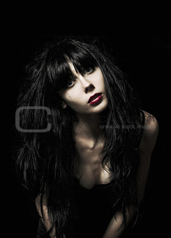 Portrait of beautiful goth girl among the darkness